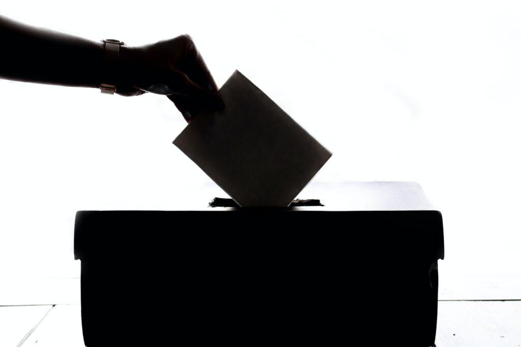 Głosowanie, dłoń wsadzająca głos do urny wysoki kontrast